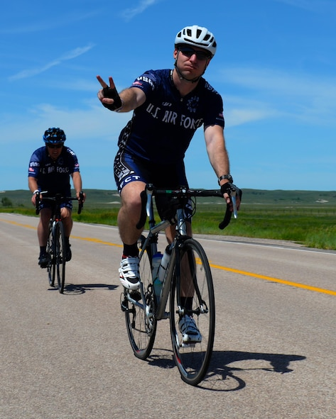 Capt. Eben Egler, a B-1 bomber weapon systems officer assigned to the 34th Bomb Squadron, and Maj. Anthony Bares, the director of inspections assigned to the 28th Bomb Wing Inspector General office, ride through the fourth pit stop during the Ride Across South Dakota bike tour near Scenic, S.D., June 4, 2017. During the first day of RASDAK, the ride included seven pit stops located eight to 20 miles away from each other over the span of 74 miles. (U.S. Air Force photo by Airman Nicolas Z. Erwin)