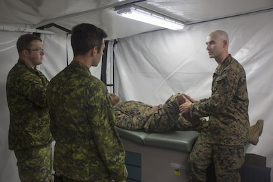 Canadian medical technicians observe U.S. Navy Lt. Cmdr. Christian Basque, a navy doctor with Marine Wing Support Squadron 472, Marine Aircraft Group 49, 4th Marine Aircraft Wing, Marine Forces Reserve, as he examines the knees of a U.S. Marine during exercise Maple Flag 50 at Canadian Forces Base Cold Lake, Alberta, June 2, 2017. During Maple Flag 50, the corpsmen's mission was to provide medical support for Marines with MWSS-473 by conducting field medical assessments. (U.S. Marine Corps photo by Lance Cpl. Niles Lee/Released)