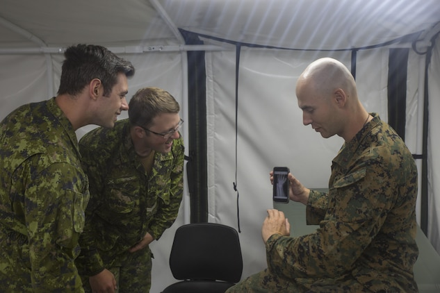 U.S. Navy Lt. Cmdr. Christian Basque, a navy doctor with Marine Wing Support Squadron 472, Marine Aircraft Group 49, 4th Marine Aircraft Wing, Marine Forces Reserve, shows pictures of X-rays from his civilian job as a sports medicine physician to Canadian medical technicians during exercise Maple Flag 50 at Canadian Forces Base Cold Lake, Alberta, June 2, 2017. Maple Flag is an annual multi-national training exercise hosted by the Royal Canadian Air Force with foreign nations training together to complete simulated combat missions. (U.S. Marine Corps photo by Lance Cpl. Niles Lee/Released)