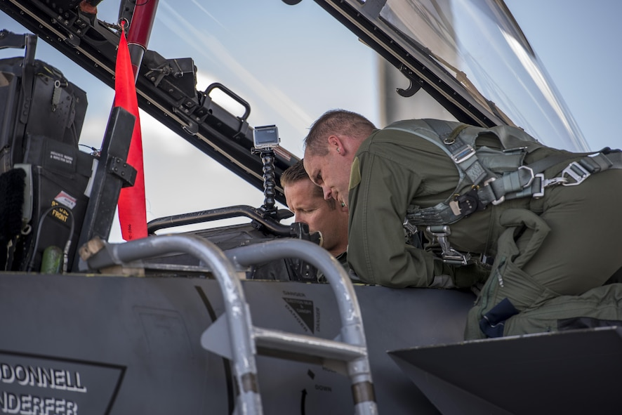 Col. Jefferson O'Donnell, 366th Fighter Wing commander, assists with getting Rich Sykes, Mountain Home mayor, situated in his seat, June 2, 2017, at Mountain Home Air Force Base, Idaho. During the orientation flight Sykes flew in the weapons system operator's seat.(U.S. Air Force Photo by Senior Airman Jeremy L. Mosier)