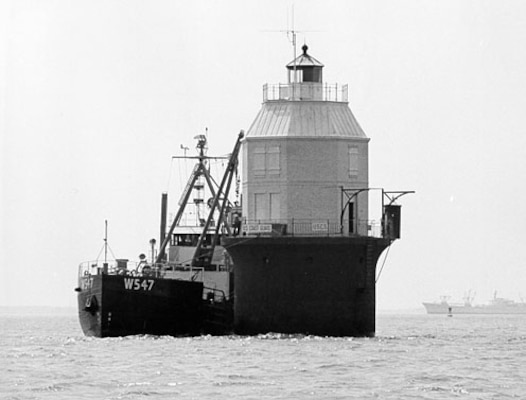 "Baltimore Light, Maryland; no photo number; caption: ""Installation of 4,600 [pound] atomic generator SNAP-7B in Baltimore Light by U.S. Coast Guard buoy tender WHITE PINE""; 20 May 1964; photo by ""Meyer, PHC, USCG."""