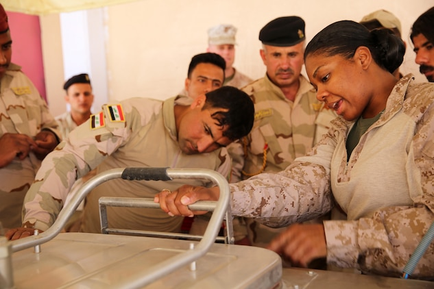 U.S. Marine Corps Staff Sgt. Shakelia Woods, a food service specialist with Special Purpose Marine Air-Ground Task Force-Crisis Response-Central Command, gives instruction on an Ozti Field Kitchen (OFK) to Iraqi soldiers with the 7th Iraqi Army Division during an Advise and Assist mission in support of Task Force Al Asad in Iraq May 4, 2017. Task Force Al Asad trains Iraqi forces with operationally relevant training, an integral aspect of Combined Joint Task Force-Operation Inherent Resolve, the global coalition to defeat ISIS in Iraq and Syria.(U.S. Marine Corps photo by Staff Sgt. Jennifer B. Poole)
