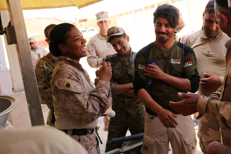 U.S. Marine Corps Staff Sgt. Shakelia Woods, a food service specialist with Special Purpose Marine Air-Ground Task Force-Crisis Response-Central Command, shares a laugh with Iraqi soldiers with the 7th Iraqi Army Division during an advise and assist mission in support of Task Force Al Asad in Iraq May 4, 2017. Task Force Al Asad trains Iraqi forces with operationally relevant training, an integral aspect of Combined Joint Task Force-Operation Inherent Resolve, the global coalition to defeat ISIS in Iraq and Syria.(U.S. Marine Corps photo by Staff Sgt. Jennifer B. Poole)