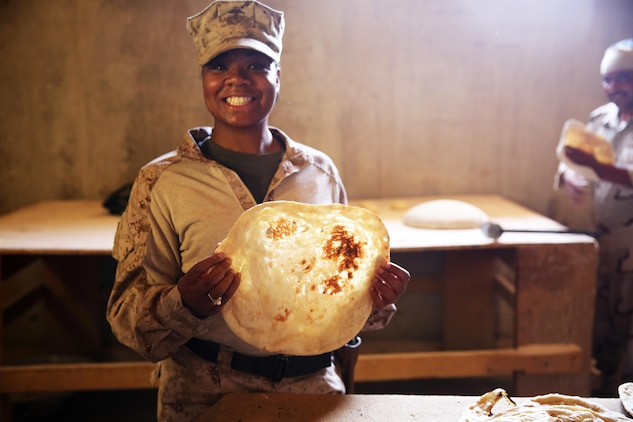 U.S. Marine Corps Staff Sgt. Shakelia Woods, a food service specialist with Special Purpose Marine Air-Ground Task Force-Crisis Response-Central Command, showcases khubuz, a traditional Iraqi flat bread, at Al Asad Air Base, Iraq, May 4, 2017. Woods instructed Iraqi soldiers with the 7th Iraqi Army Division on capabilities and employment of an Ozti Field Kitchen (OFK) during an advise and assist mission in support of Task Force Al Asad. Task Force Al Asad trains Iraqi forces with operationally relevant training, an integral aspect of Combined Joint Task Force-Operation Inherent Resolve, the global coalition to defeat ISIS in Iraq and Syria. (U.S. Marine Corps photo by Staff Sgt. Jennifer B. Poole)