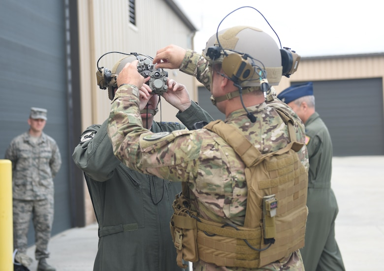 During a tour June 10, 2017, of the 193rd Special Operations Wing, Middletown, Pennsylvania, Staff Sgt. Shawn Kobel, a security forces specialist with the 193rd Special Operations Security Forces Squadron, shows U.S. Air Force Lt. Gen. Brad Webb (left), commander of Air Force Special Operations Command, how troops wear and operate the op-score helmet. These helmets are relatively new to the unit and include earmuffs and a radio, as well as nighttime and thermal vision. (U.S. Air National Guard photo by Senior Airman Julia Sorber/Released)