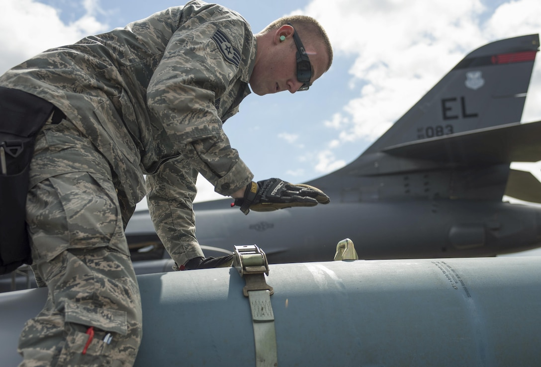 U.S. Air Force Staff Sgt. Matthew Milbrecht, 28th Aircraft Maintenance Squadron weapons load crew chief, straps down a BDU-56, (inert munition) a general purpose unguided conventional weapon, at Royal Air Force Fairford, U.K., June 7, 2017. Airmen from the 28th Aircraft Maintenance Squadron are supporting bomber assurance and deterrence missions in the European theatre that combine training opportunities and greatly improve interoperability among participating NATO allies and regional partners. (U.S. Air Force photo by Airman 1st Class Randahl J. Jenson)