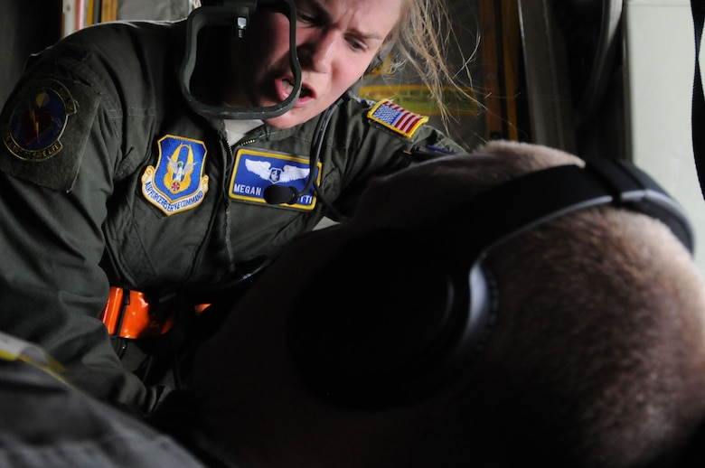 1st Lt. Megan Mancinotti, a crew member with the 445th Aeromedical Evacuation Squadron here, gives instructions to a Citizen Airman simulating a patient for a joint training mission here, June 7, 2017. The 445th AES trained for two hours while airborne to simulate a real-world scenario. (U.S. Air Force photo/Senior Airman Joshua Kincaid)