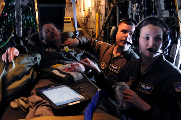 445th Aeromedical Evacuation Squadron crew members, 1st Lt. Emily Perkins and Staff Sgt. Brandon Croghan, check the pulse of a Citizen Airman portraying a patient for a joint training mission here, June 7 2017. The 445th AES trained for two hours while airborne to simulate a real-world scenario. (U.S. Air Force photo/Senior Airman Joshua Kincaid)