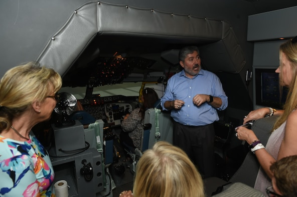 Tony Valerio, CAE Systems instructor pilot, show the 2017 Altus honorary commanders a pilot simulator for the U.S. Air Force KC-135 Stratotanker during an immersion tour, May 31, 2017 at Altus Air Force Base, Oklahoma. The honorary commanders took turns flying and landing the simulator to demonstrate the capability of the training system during their Immersion tour. (U.S. Air Force Photo by Senior Airman Kirby Turbak/Released.)
