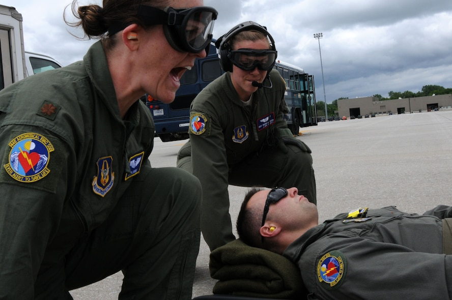 445th Aeromedical Evacuation Squadron crew members, Maj. Jen Cowie (left) and Staff Sgt. Nicole Karsten (right), prepare to lift a Citizen Airman simulating a patient for a joint training mission here, June 7, 2017. The 445th AES trained for two hours while airborne to simulate a real-world scenario. (U.S. Air Force photo/Senior Airman Joshua Kincaid)