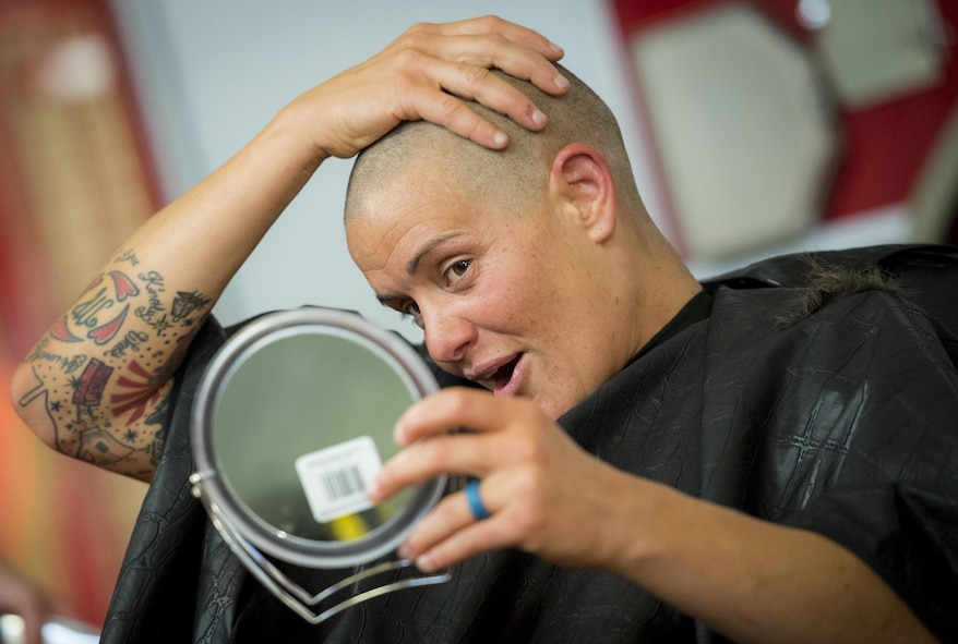 Amber Turek, a 96th Test Wing firefighter, checks out her skull after having her head shaved June 8 at Eglin Air Force Base, Fla.  Approximately 20 firefighters shaved their heads to raise awareness and funds for their crew mate, Terrance Curry, whose battled cancer continuously for 11 months.  (U.S. Air Force photo/Samuel King Jr.)