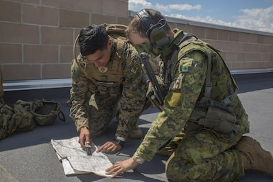 Cpl. Daniel A. Reyes (left), a joint fires observer with 3rd Brigade, 3rd Air Naval Gunfire Liaison Company, Force Headquarters Group, Marine Forces Reserve, kneels alongside Canadian Army Capt. Ethan McDonald (right), a joint terminal attack controller with Y Battery, 2nd Regiment, Royal Canadian Horse Artillery and points out target coordinates on a map at Canadian Manoeuvre Training Center, in Wainwright, Alberta, Canada, during exercise Maple Resolve 17, May 26, 2017. During the exercise the Marines from 3rd ANGLICO worked with the Canadian Army, calling simulated artillery to preplanned targets.