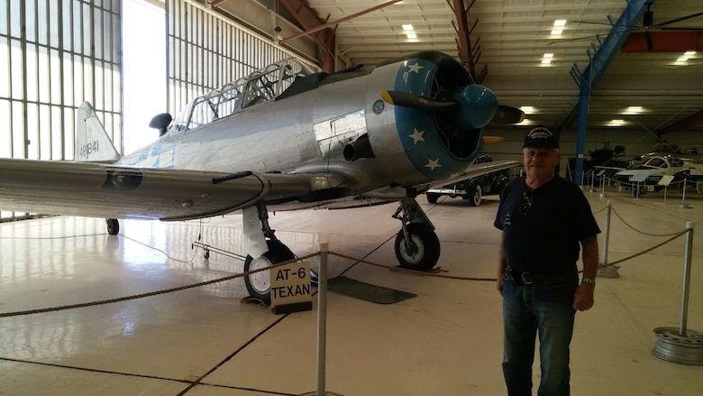 "Col. (ret) Forrest ""Dutch"" Kissinger poses in front of a T-6 Texan. Kissinger enlisted in the Air Force in 1949, he later earned the opportunity to commission and become a pilot."