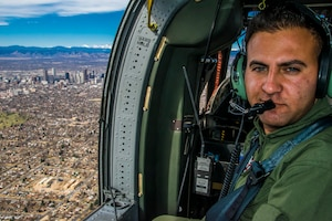 During a flight from Buckley Air Force Base, and traveling over downtown Denver, Sgt. Hazem Al-Qaise, an RJAF crew chief, takes his position as a crew chief, in the jump seat, March 16, 2017. Members of rotory-wing aviation units from the Royal Jordanian Air Force and the Colorado Army National Guard share knowledge about the UH-60 Black Hawk and sling-load operations. The RJAF members traveled to Colorado as part of the National Guard State Partnership Program.