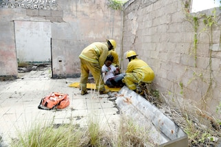 Fire officers from the Bridgetown Fire Department assess and assist a volunteer actor during a mass casualty drill at the site of the former Glendairy Prison. The scenario was based on the idea that an earthquake caused a hotel to collapse and local emergency services and Barbados Defence Force (BDF) personnel were working together to rescue and treat survivors. Tradewinds 2017 Regional Observer and Assessment Team (ROAT) members from multiple countries watched the exercise to take notes and create an assessment for Barbadian officials. The report will contain ideas of ways emergency services might be able to improve response procedures. Tradewinds is a joint, combined exercise conducted in conjunction with partner nations to enhance the collective abilities of defense forces and constabularies to counter transnational organized crime, and to conduct humanitarian and disaster relief operations. (U.S. Navy photo by Mass Communication Specialist 1st Class Melissa K. Russell/Released)