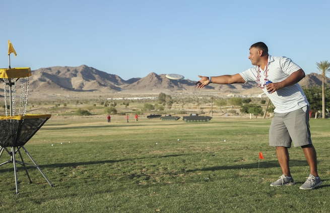 Staff Sgt. Stephen Chevez, radio chief, Marine Corps Communication-Electronics School, attempts to throw a Frisbee into a goal, during the annual Pro and Glow golf tournament hosted by Marine Corps Community Services at the Desert Winds Golf Course aboard the Marine Corps Air Ground Combat Center Twentynine Palms, Calif., June 2. MCCS hosted the event, which featured presentations from a professional golfer and a professional Frisbee golfer for the purpose of introducing Combat Center patrons to the sports and showcasing the golf and Frisbee golf courses aboard the base.