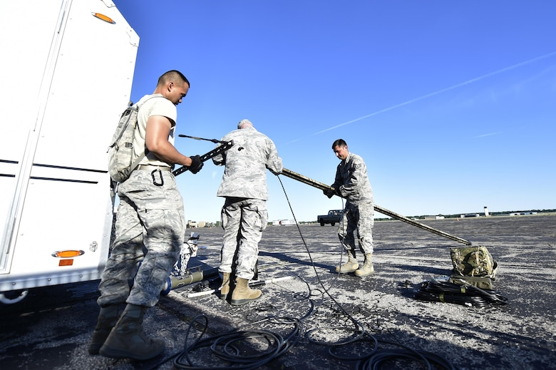 Senior Airman Zyrus Medina, Tech. Sgt. Joshua Pospisil, and Staff Sgt. Ronny Cox, 821st Contingency Response Support Squadron, set up the radio frequency transmission system during Exercise Turbo Distribution 17-02, June 7, 2017, at Battle Creek Air National Guard Base, Mich.  Turbo Distribution 17-2 is an U.S. Transportation Command exercise designed to assess the Joint Task Force-Port Opening's ability to deliver and distribute cargo during humanitarian and disaster relief operations. (U.S. Photo by Tech. Sgt. Liliana Moreno/Released)