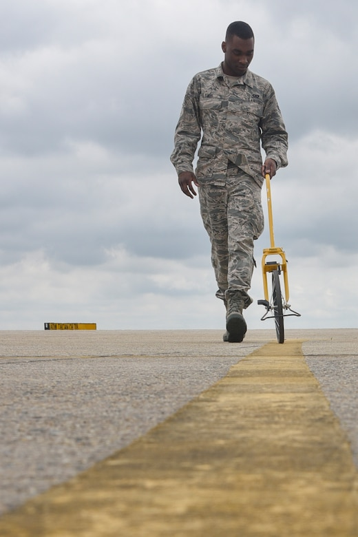 Airman 1st Class Isaiah Davis, 89th Operations Support Squadron airfield manager, measures a flightline marking at Joint Base Andrews, Md., June 7, 2017. Inspecting these markings and making sure they are within regulations ensures pilots can navigate the flightline in a safe manner. (U.S. Air Force photo by Airman 1st Class Valentina Lopez)