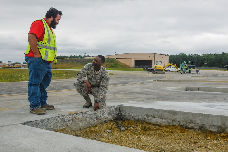 Airman 1st Class Isaiah Davis, right, 89th Operations Support Squadron airfield manager, works with construction personnel during flightline repairs at Joint Base Andrews, Md., June 7, 2017. Airfield management coordinates all flightline operations with many units including air traffic control, security forces and civil engineers.  (U.S. Air Force photo by Airman 1st Class Valentina Lopez)