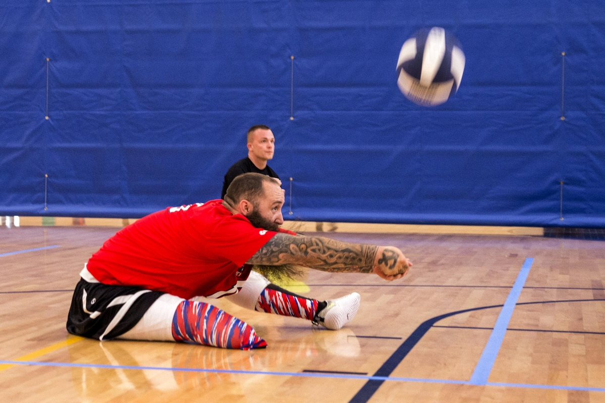 A retired sailor hits a ball during sitting volleyball drills.