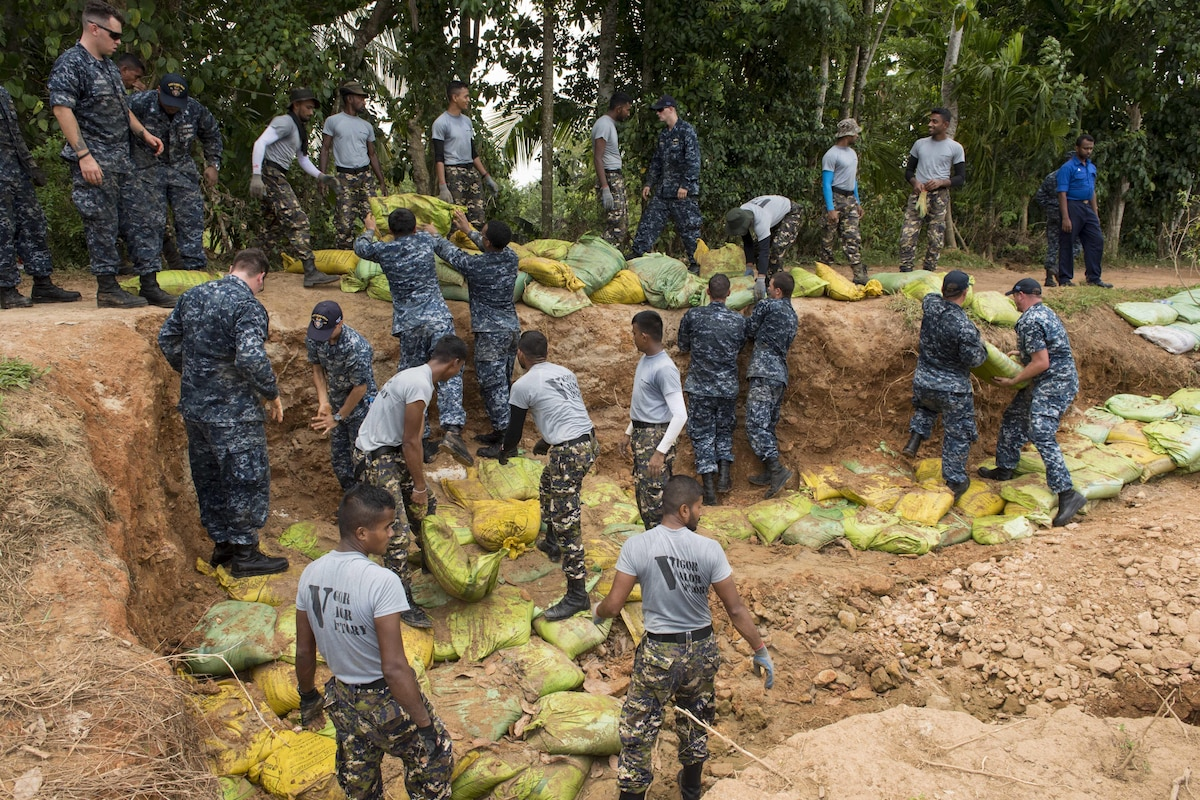 Sailors work with Sri Lankan marines to repair a levee.