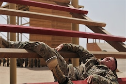 Spc. Thomas Jancosek, a Soldier with 3rd Armored Brigade Combat Team, 1st Cavalry Division, competitor in the U.S. Army Central Best Warrior, perseveres through one of the last obstacles on the air assault obstacle course at Camp Buehring, Kuwait, May 23. Soldiers had to climb, crawl, and swing their way to the end of the course. (Photo by U.S. Army Sgt. Kelly Gary, 29th Infantry Division Public Affairs)