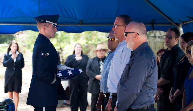 A MacDill Air Force Base U.S. Air Force Honor Guardsman presents a folded flag to the family of a veteran during a funeral service at Florida National Cemetery, June 8, 2017. During the funeral, Honor Guardsmen performed a flag fold and presented it to the family while, on behalf of the President of the United States, thanking them for their service. (U.S. Air Force Photo by Airman 1st Class Rito Smith)