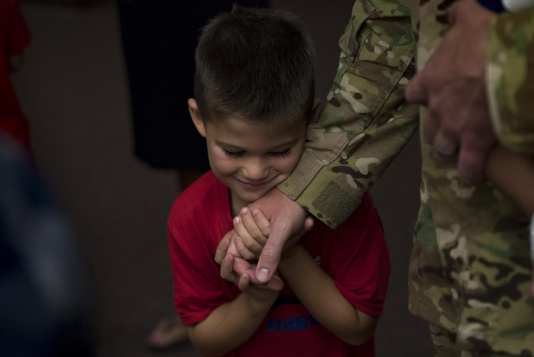 Luke Rynbrandt, holds the hand of his father, Capt. Kevin Rynbrandt, 41st Rescue Squadron HH-60G Pave Hawk pilot, as he returned home from a deployment, June 8, 2017, at Moody Air Force Base, Ga. The 41st and 71st Rescue Squadrons were recently deployed to Southwest Asia where they provided combat search and rescue capabilities in support of Operation Inherent Resolve. (U.S. Air Force photo By Airman 1st Class Daniel Snider)