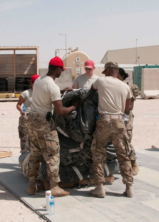 Soldiers of the 824th Quartermaster Company stack parachutes used for aerial delivery at Al Udeid Air Base, Qatar on April 19, 2017. Aerial delivery operations are essential for getting supplies to troops in the Middle East when conventional means of transportation are not feasible. (U.S. Army photo by Sgt. Jeremy Bratt)