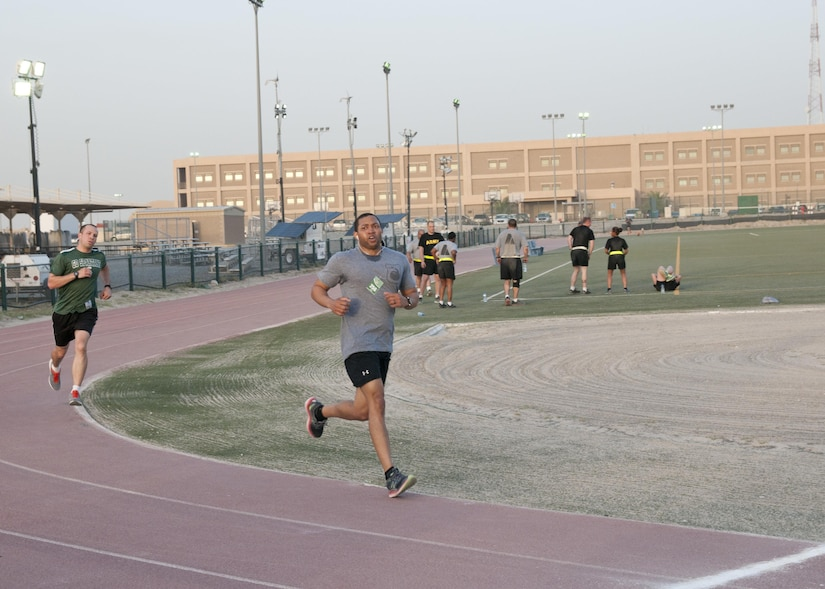 """Staff Sgt. Mitchum Vanrooyen, of the 369th Sustainment Brigade crosses the finish line in the inaugural Harlem Hellfighter 5K run, held at Camp Arifjan, Kuwait on June 2, 2017. The event was held to celebrate the 104th anniversary of the formation of the historic New York National Guard unit. The unit was given their historic nickname """"Hellfighters"""" by their German opponents in WWI for their remarkable prowess on the battlefield. (U.S. Army photo by Sgt. Jeremy Bratt)"""