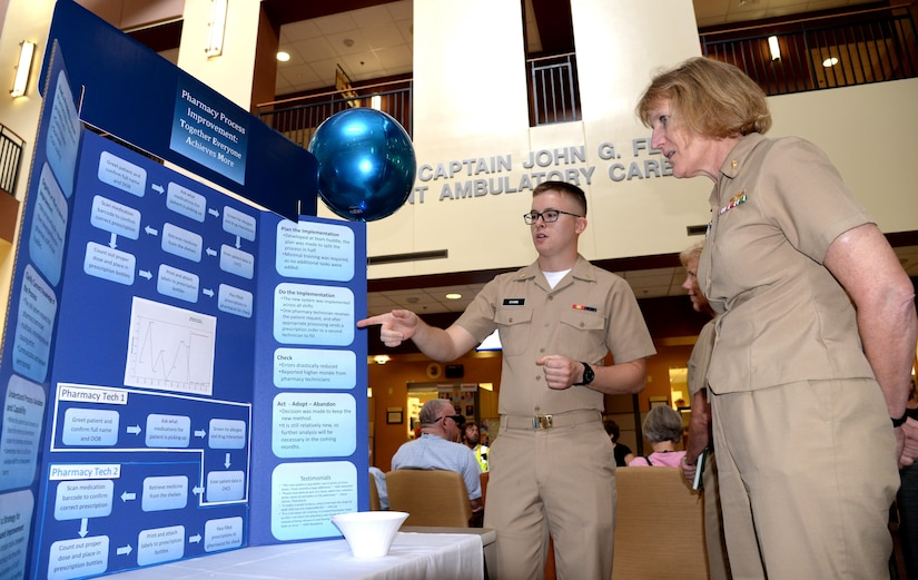 U.S. Navy Ensign Matthew Evans, officer in training for submarine warfare qualification, serving as support staff for the pharmacy at Naval Health Clinic Charleston, shows NHCC Commanding Officer, Capt. Elizabeth Maley, the pharmacy's new procedure for filling prescriptions during Naval Health Clinic Charleston's 2nd Continuous Performance Improvement Fair here, June 2. The procedure minimizes errors while improving wait times. Evan's display was one of many at the CPI fair designed to highlight the strides taken by NHCC staff members to improve the quality, education and safety of health care for NHCC's patients.