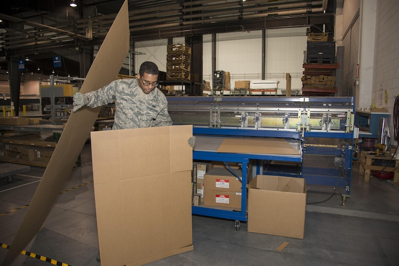 Senior Airman Gerard Pinckney, 436th Aerial Port Squadron traffic management specialist, picks up a piece of cardboard ready to be installed into a box Jan. 12, 2017, at the aerial port on Dover Air Force Base, Del. Making boxes as needed reduces the amount of storage space required, limits the amount of materials that need to be stored and reduces material waste. (U.S. Air Force photo by Senior Airman Aaron J. Jenne)
