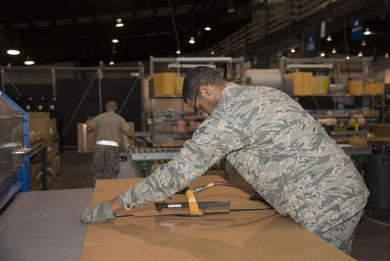Senior Airman Gerard Pinckney, 436th Aerial Port Squadron traffic management specialist, staples two pieces of a cardboard box together Jan. 12, 2017, at the aerial port on Dover Air Force Base, Del. Using the box-making machine, Airmen can calculate dimensions and create a shipping box in only a few minutes. (U.S. Air Force photo by Senior Airman Aaron J. Jenne)