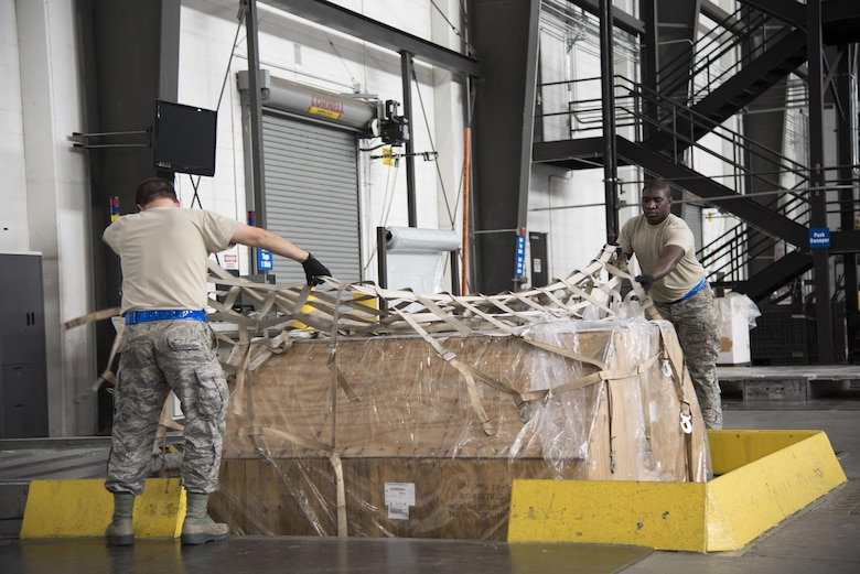 Cargo processors Senior Airman Jeffrey Korpics, 436th Aerial Port Squadron, and Senior Airman Terrence Roberts, 46th APS, secure a pallet Jan. 12, 2017, at the aerial port on Dover Air Force Base, Del. Each pallet- building station lowers for improved ergonomics and safety. (U.S. Air Force photo by Senior Airman Aaron J. Jenne)