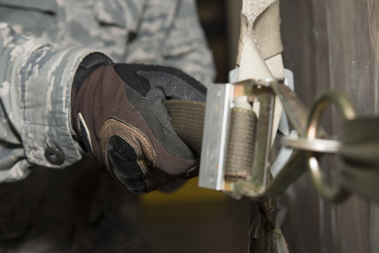 Staff Sgt. Travis Thompson, 436th Aerial Port Squadron cargo processing supervisor, tightens a strap on a pallet Jan. 12, 2017, at the aerial port on Dover Air Force Base, Del. Pallets are loaded to meet weight and size goals in order to maximize aircraft loads and weight distribution. (U.S. Air Force photo by Senior Airman Aaron J. Jenne)