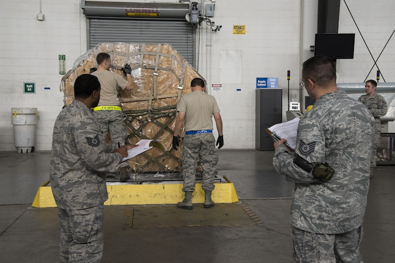 Tech. Sgts. Randie Page and Jeffrey Kach, 436th Aerial Port Squadron Air Transportation Standardization and Evaluations Program evaluators, observe Airmen build a pallet Jan. 12, 2017, at the aerial port on Dover Air Force Base, Del. The ATSEP program was established in 2016 to realign the existing evaluations program with the Air Force Inspection System. (U.S. Air Force photo by Senior Airman Aaron J. Jenne)