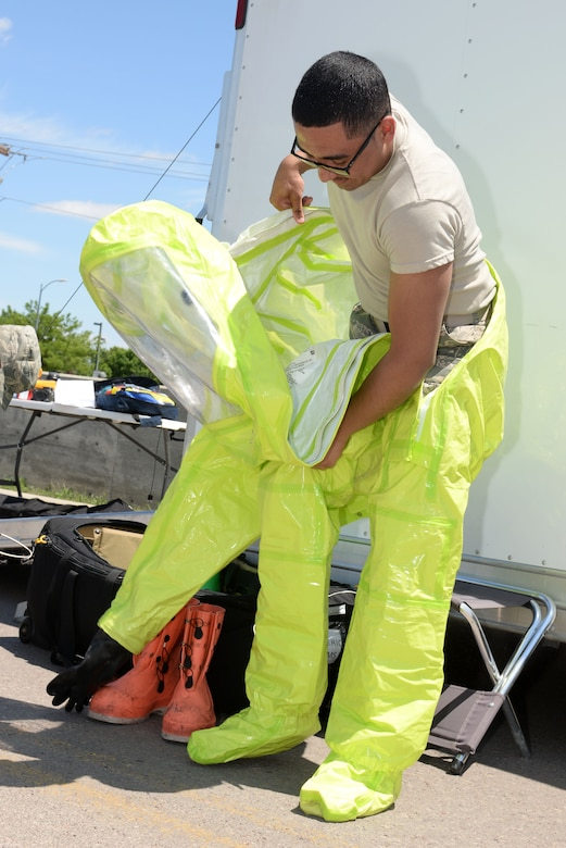 Airman 1st Class Roderick Williams, a bioenvironmental engineering journeyman assigned to the 28th Medical Operations Squadron, dons a chemical protection suit during an exercise at Ellsworth Air Force Base, S.D., June 7, 2017. During the exercise, the bioenvironmental engineering flight responded to a simulated chemical, biological, radiological, and nuclear environmental (CBRNE) threat to determine if it was an immediate threat to the installation. (U.S. Air Force photo by Staff Sgt. Hailey Staker)