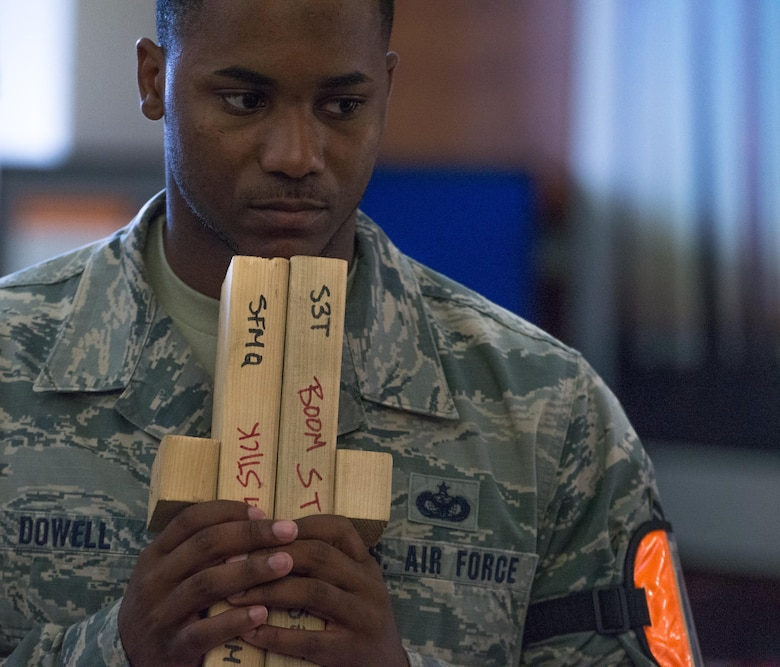 U.S. Air Force Staff Sgt. Rodney Dowell, 36th Security Forces Squadron wing inspection team member, holds boom sticks during an emergency management exercise May 11, 2017 at Andersen Air Force Base, Guam. Boom sticks are used to produce loudpercussive sounds, similar to that of gunfire, to enhance the realism of simulated active-shooter scenarios. (U.S. Air Force photo by Airman 1st Class Jacob Skovo)