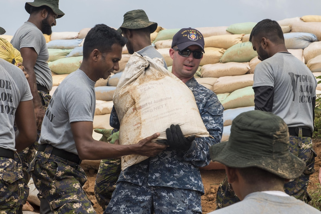 Fire Controlman from USS Lake Erie works with Sri Lankan marines to repair levees in Matara, Sri Lanka, during humanitarian assistance operations in wake of severe flooding and landslides, June 12, 2017 (U.S. Navy/Joshua Fulton)