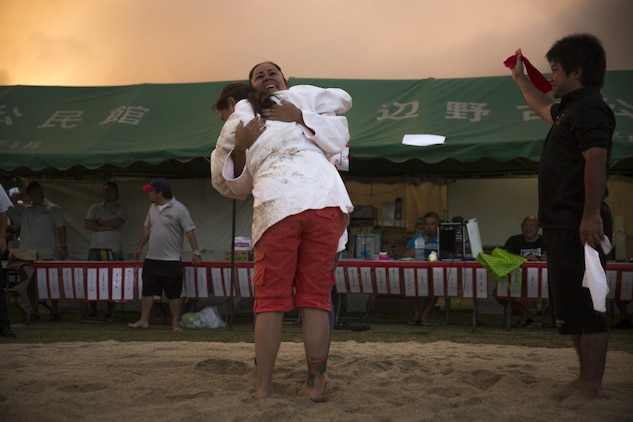 Two competitors embrace each other after their bout, June 10, 2017, during the annual Henoko Okinawa-Style Sumo Tournament, at Mae-No-Hama Field, in Henoko, Okinawa, Japan. During a bout, competitors try to earn points by making their opponent fall into the dohyo, or sandy pit, without striking or letting go of each other's belts. The first to gain two points is the victor. Okinawa-style sumo wrestling, also known as kakuriki, is a combination of western wrestling and traditional Japanese sumo and judo, according to Fumio Iha, Camp Schwab's community relations specialist. (U.S. Marine Corps photo by Lance Cpl. Andy Martinez)