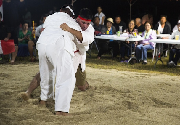"""Lance Cpl. Giovanni L. Ramires (right center) leg sweeps his opponent, June 10, 2017, during the annual Henoko Okinawa-Style Sumo Tournament at Mae-No-Hama Field in Henoko, Okinawa, Japan. During a bout, competitors try to earn points by making their opponent fall into the """"dohyo,"""" or sandy pit, without striking or letting go of each other's belts. The first to gain two points is the victor. Okinawa-style sumo wrestling, also known as kakuriki, is a combination of western wrestling and traditional Japanese sumo and judo, according to Fumio Iha, Camp Schwab's community relations specialist. Ramires is a native of Johnstown, Pennsylvania, and an intelligence specialist with 3rd Intelligence Battalion, III Marine Expeditionary Force Headquarters Group. (U.S. Marine Corps photo by Lance Cpl. Andy Martinez)"""