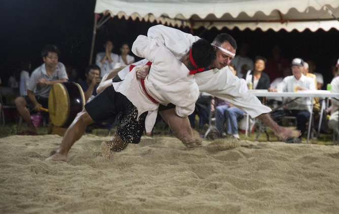 Lt. Col. James Dorlon (right center) slams his opponent to the ground, June 10, 2017, during the annual Henoko Okinawa-Style Sumo Tournament, at Mae-No-Hama Field, in Henoko, Okinawa, Japan. During a bout, competitors try to earn points by making their opponent fall into the dohyo, or sandy pit, without striking or letting go of each other's belts. The first to gain two points is the victor. Dorlon is a native of Beaverton, Oregon, and the commanding officer of Jungle Warfare Training Center, 3rd Marine Division, III Marine Expeditionary Force. (U.S. Marine Corps photo by Lance Cpl. Andy Martinez)