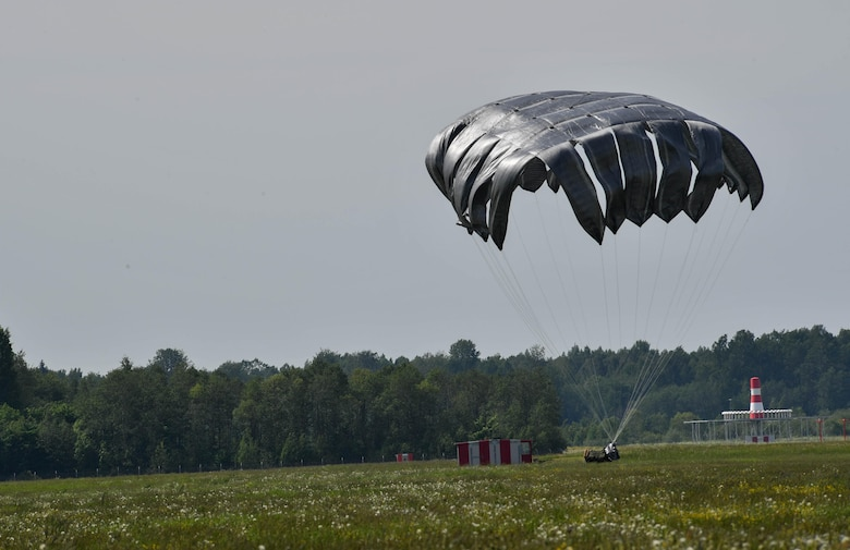 A pallet of equipment lands on the ground after being dropped out of a U.S. Air Force C-130J Super Hercules during exercise Saber Strike 17 on Lielvārde Air Base, Latvia, June 7, 2017. The 435th Contingency Response Group from the 435th Air Ground Operations Wing at Ramstein Air Base, Germany, dropped the bundle to practice assessing an area for aircraft landings. Saber Strike 17 continues to increase participating nations' capacity to conduct a full spectrum of military operations. (U.S. Air Force photo by Senior Airman Tryphena Mayhugh)