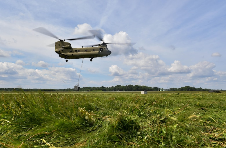 A U.S. Army CH-47 Chinook helicopter lifts a bundle into the air for the U.S. Air Force 435th Contingency Response Group's sling load operation during exercise Saber Strike 17 at Lielvarde Air Base, Latvia, June 10, 2017. The 435th CRG Airmen worked alongside the U.S. Army and NATO military members throughout the exercise. Saber Strike 17 continues to increase participating nations' capacity to conduct a full spectrum of military operations.  (U.S Air Force photo by Senior Airman Tryphena Mayhugh)
