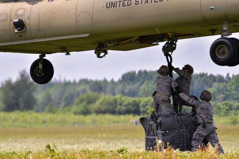 U.S. Air Force Airmen assigned to the 435th Contingency Response Group hook a bundle to the bottom of a U.S. Army CH-47 Chinook for the 435th CRG's sling load operation during exercise Saber Strike 17 at Lielvarde Air Base, Latvia, June 10, 2017. The Chinook raised and then set down the bundle, allowing for a new team of 435th CRG Airmen to practice rigging the bundle next. The combined training opportunities that Saber Strike 17 provides greatly improve interoperability among participating NATO allies and key regional partners.  (U.S Air Force photo by Senior Airman Tryphena Mayhugh)