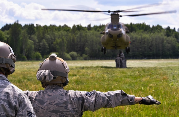 U.S. Air Force Staff Sgt. Edgar Cerrillo, 435th Security Forces Squadron Ground Combat Readiness Training Center instructor, gives hand signals to a U.S. Army CH-47 Chinook for the 435th Contingency Response Group's sling load operation during exercise Saber Strike 17 at Lielvarde Air Base, Latvia, June 10, 2017. 435th CRG Airmen connected a bundle to the Chinook to practice properly rigging cargo for a sling load operation. Saber Strike 17 promotes regional stability and security, while strengthening partner capabilities and fostering trust. (U.S Air Force photo by Senior Airman Tryphena Mayhugh)