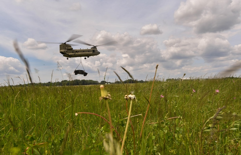 A U.S. Army CH-47 Chinook helicopter carries a high mobility multipurpose wheeled vehicle for the U.S. Air Force 435th Contingency Response Group's sling load operation during exercise Saber Strike 17 at Lielvarde Air Base, Latvia, June 10, 2017. The 435th CRG Airmen worked alongside the U.S. Army and NATO military members throughout the exercise. Saber Strike 17 continues to increase participating nations' capacity to conduct a full spectrum of military operations.  (U.S Air Force photo by Senior Airman Tryphena Mayhugh)