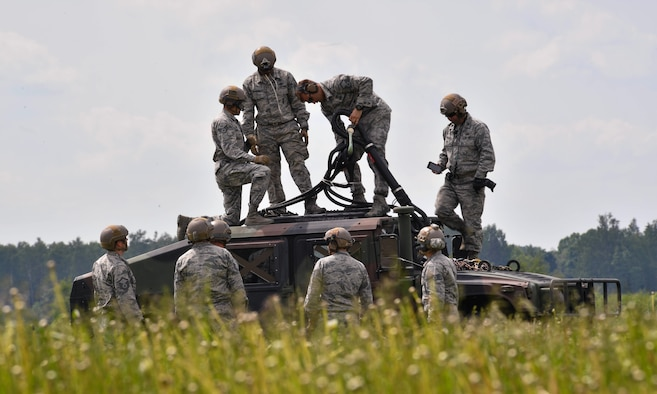 U.S. Air Force Airmen assigned to the 435th Contingency Response Group prepare a high mobility multipurpose wheeled vehicle to be picked up by a U.S. Army CH-47 Chinook for the 435th CRG's sling load operation during exercise Saber Strike 17 at Lielvarde Air Base, Latvia, June 10, 2017. The 435th CRG Airmen practiced rigging the HUMVEE and a bundle multiple times to practice for a sling load operation. Saber Strike 17 continues to increase participating nations' capacity to conduct a full spectrum of military operations. (U.S Air Force photo by Senior Airman Tryphena Mayhugh)