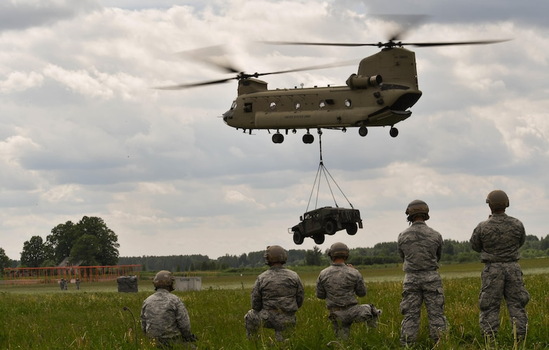 U.S. Air Force Airmen assigned to the 435th Contingency Response Group watch a high mobility multipurpose wheeled vehicle suspended from a U.S. Army CH-47 Chinook for the 435th CRG's sling load operation during exercise Saber Strike 17 at Lielvarde Air Base, Latvia, June 10, 2017. The 435th CRG Airmen rigged the HUMVEE to the Chinook and were watching to make sure it had been rigged properly. Saber Strike 17 highlights the inherent flexibility of ground and air forces to rapidly respond to crises allowing for the right presence where it is needed, when it is needed. (U.S Air Force photo by Senior Airman Tryphena Mayhugh)