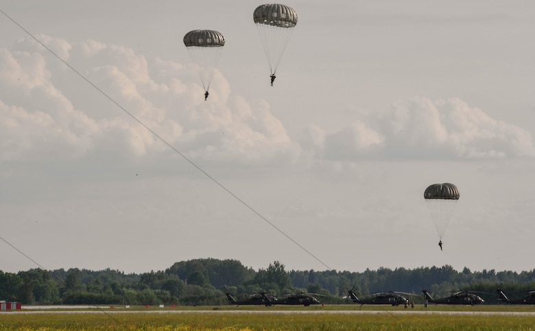 U.S. Air Force Airmen assigned to the 435th Contingency Response Group float to the ground after jumping from a U.S. Army CH-47 Chinook for the 435th Contingency Response Group's sling load during exercise Saber Strike 17 at Lielvarde Air Base, Latvia, June 10, 2017. The 435th CRG sends paratroopers to austere locations to determine if an area can be safely used as an airfield. Saber Strike 17 highlights the inherent flexibility of ground and air forces to rapidly respond to crises allowing for the right presence where it is needed, when it is needed. (U.S Air Force photo by Senior Airman Tryphena Mayhugh)